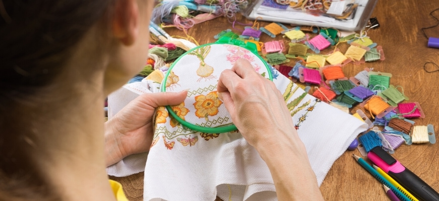 A back shot of a woman embroidering cool designs of stitches