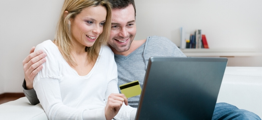 Couple looking on laptop,while woman's hand holding a credit card.