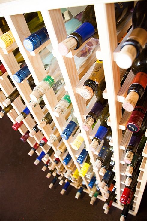 A close-up photograph of many wine bottles on a wooden rack in a restaurant.