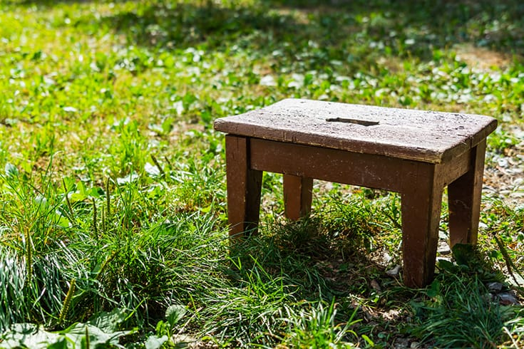 Wooden step stool on a meadow in the sunshine summer