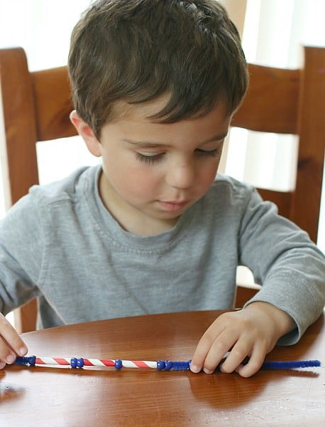 little boy sitting down on wooden chair holding Patriotic Necklace on the table