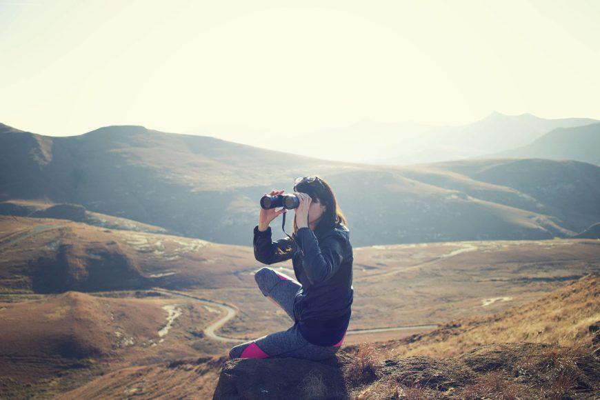 Woman using binoculars on the mountain