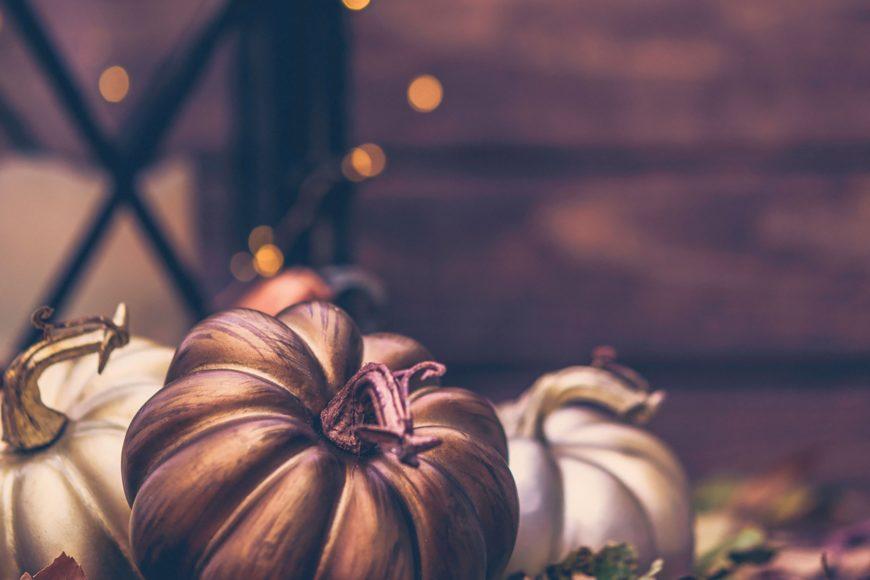 Three pumpkins centerpieces in blurry wooden background