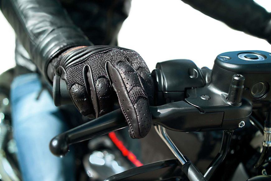 Close up image of a motorcycle rider with hand gloves