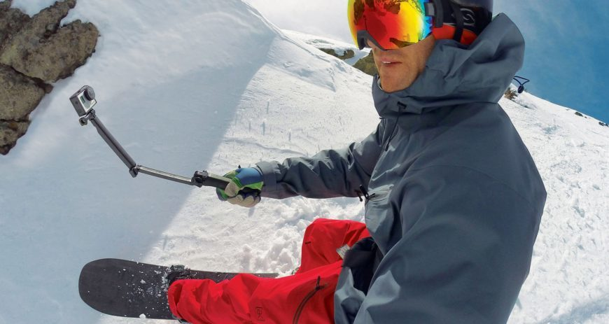 Man snowboarding while holding a gopro