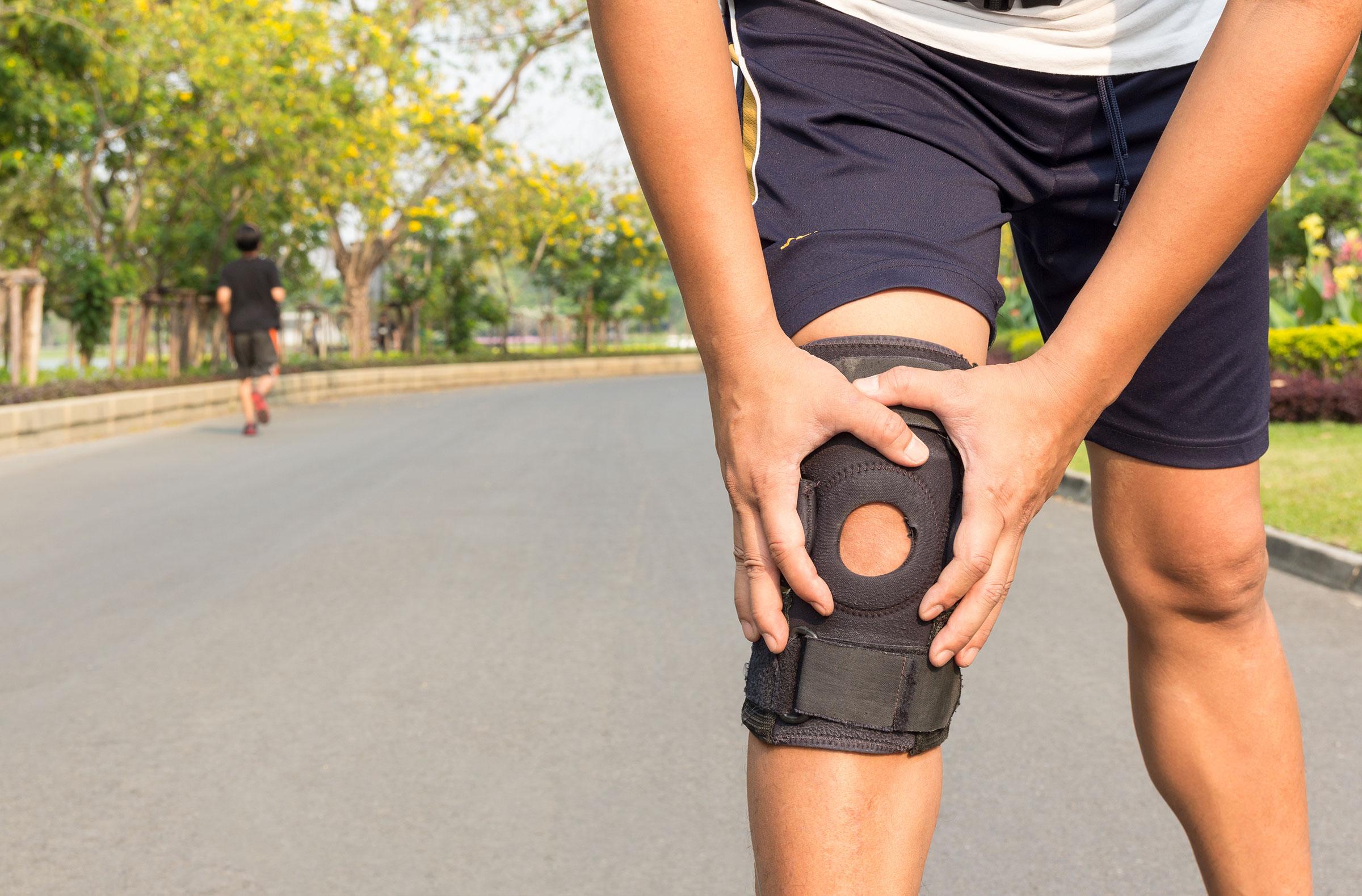 Crop image of man's knee with knee braces