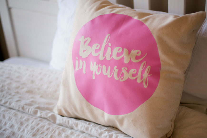Pillow case with printed pink cirlcle with words Believe in yourself at the center