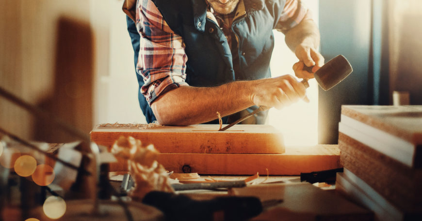 Man using wood carving tools with smile