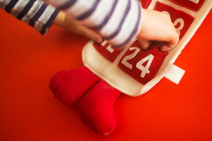 Kid's hand putting something on christmas advent calendar cover