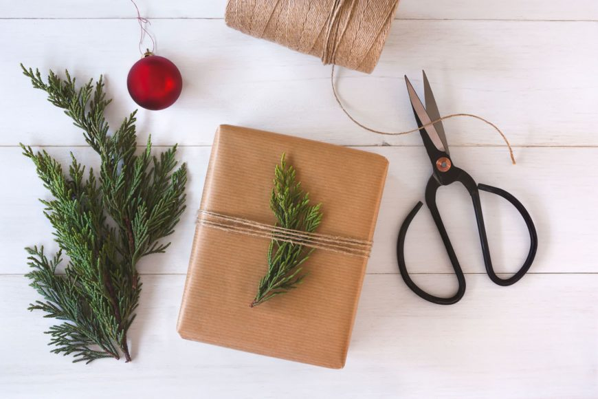 Scissor, string, pine tree leaves and brown note tide with a pine tree leaves.