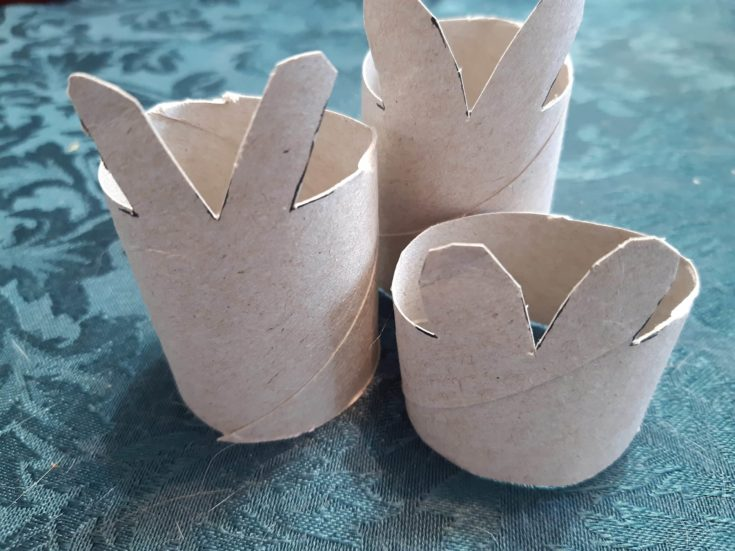 Three cardboard tubes with a cutted bunny ear patterns.