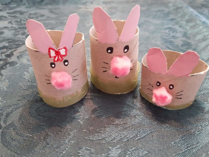 Three cardboard tube bunnies with pink pompom noses and added grass features below.