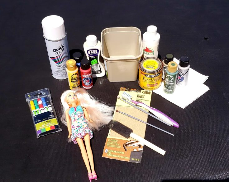 Materials needed for DIY Barbie Zombie - Plastic Doll + Plastic Tub + Dye/Stain Paints + Small Paint Brush + Acrylic Paints + Gray Spray Paint + Paper Towels