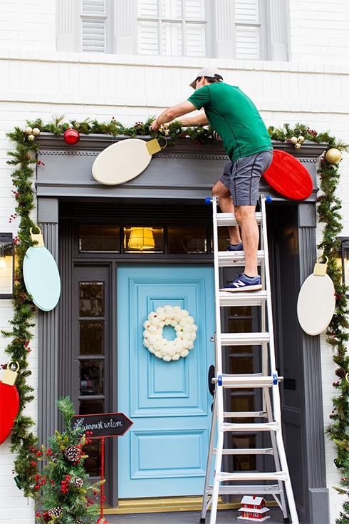 man on the ladder putting DIY Wooden Lights Garland