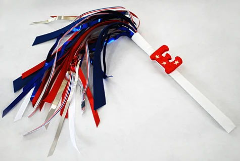 Sparkless sparklers for kids for the Fourth of July using chopsticks, ribbon and party garland