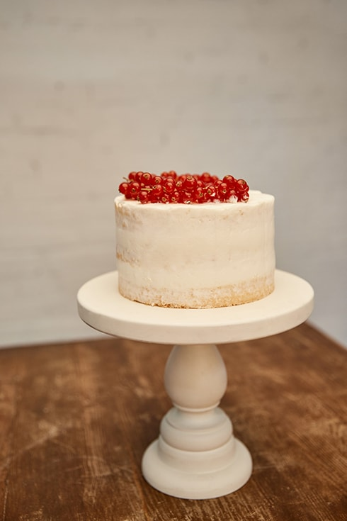 Sweet sponge cake with cream and juicy redcurrant on cake stand on wooden table