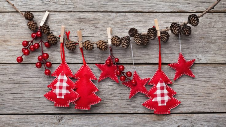 Christmas and New Year decorations made of felt are hanging on stick with pinecones, rustic wooden background, copy space