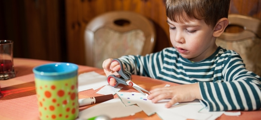 Boy kid holding scissor with papers on the table