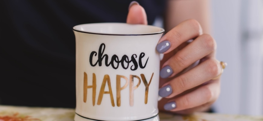 """Woman's hand holding mug with a printed word """"Choose Happy"""""""