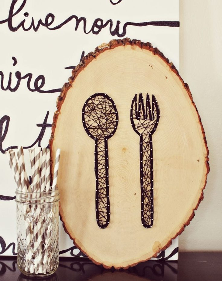 String art cutlery design on round wood plank.