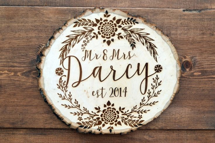 Gorgeous balsa wood slice and engraved with hand written calligraphy design of a couple's name and flowers for borders.