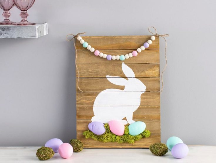 A DIY painted wooden sign, painted with white rabbit and colorful easter eggs using clay and plastic moss green.
