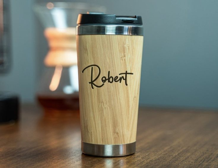A personalized travel tumbler with name engraved on the bamboo clad tumbler.