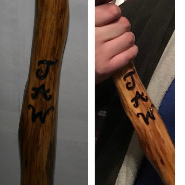 Personalized wood burned text on a walking stick.