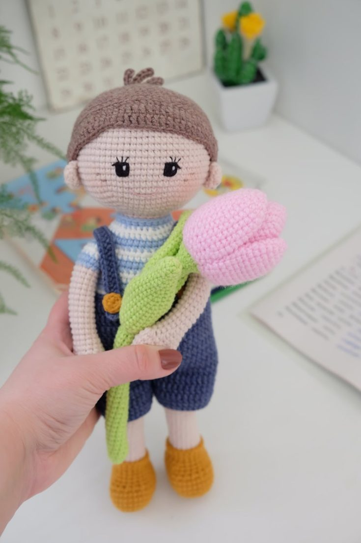 Close up shot of woman's hand holding a crocheted doll with bouquet of crocheted tulips.