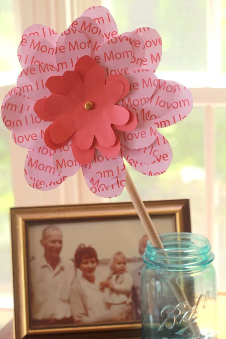 A floral pinwheel for mom put on a mason jar and a picture frame at background.