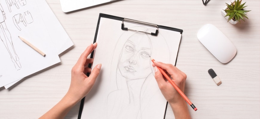 Woman's hand sketching on white paper with drawing materials on white table