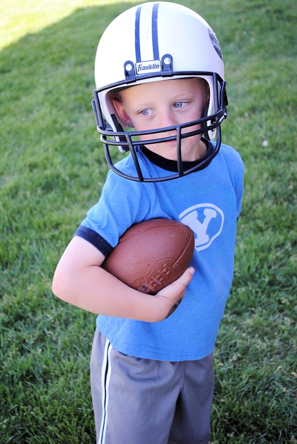 Little boy in blue t-shirt and gray shorts,holding a football and wears a football helmet in an open ground.