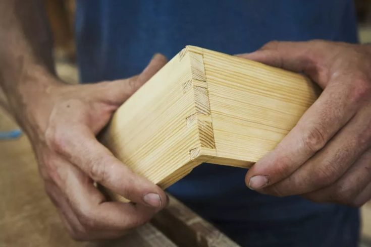 Close up of person working a boat builders workshop joining together two pieces of wood.
