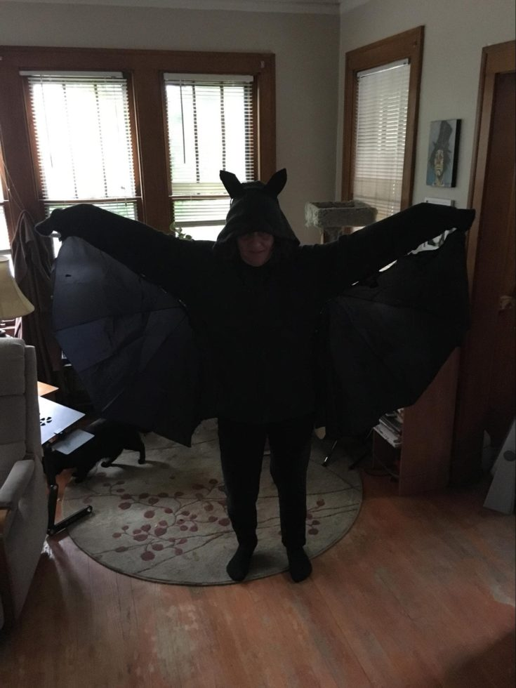 a woman wearing all black bat halloween costume