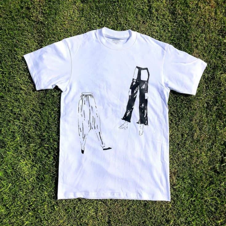 a white t-shirt on placed on the grass with denim jeans design