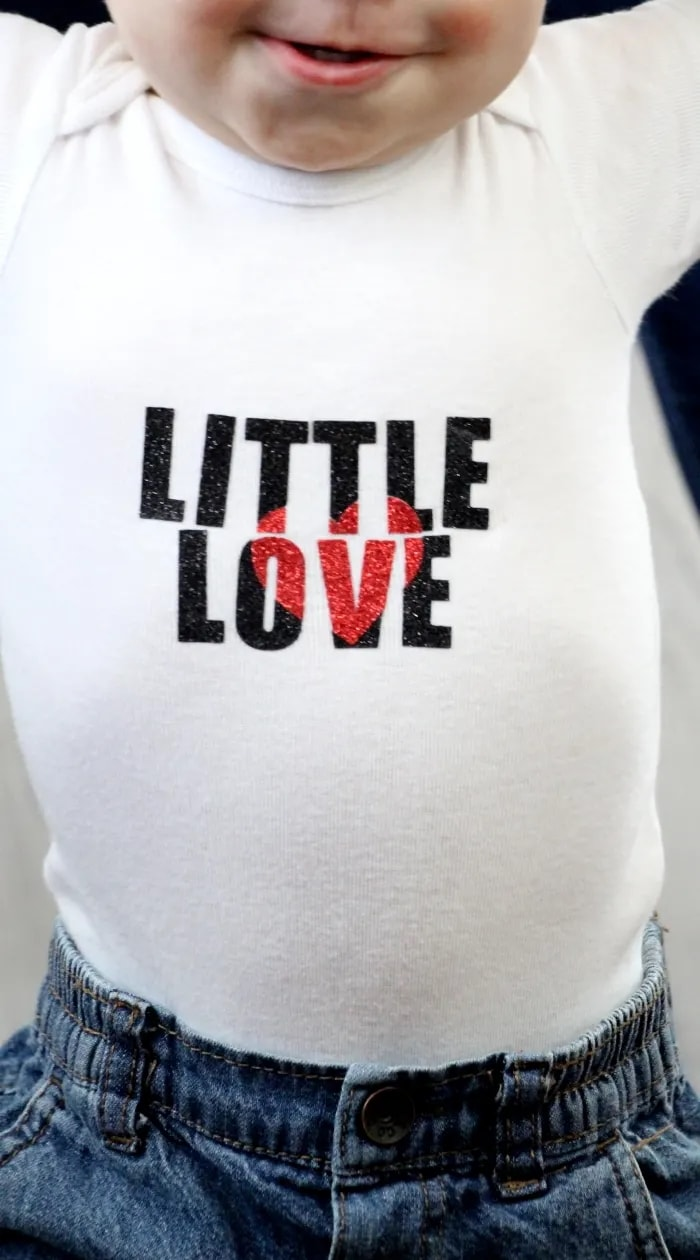 Glittery heat press vinyl text on baby's white shirt