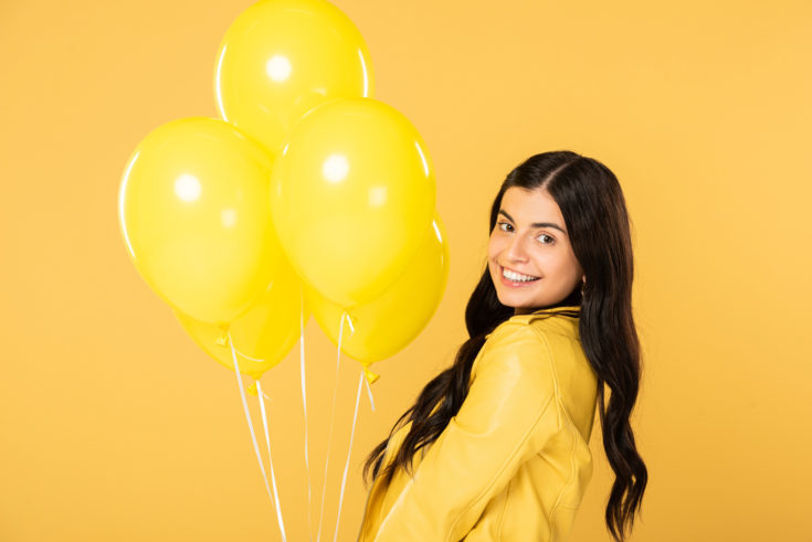 Brunette happy woman holding yellow balloons, isolated on yellow