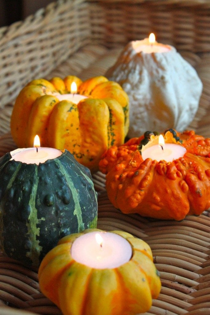 Candles in colorful gourds thanksgiving centerpiece