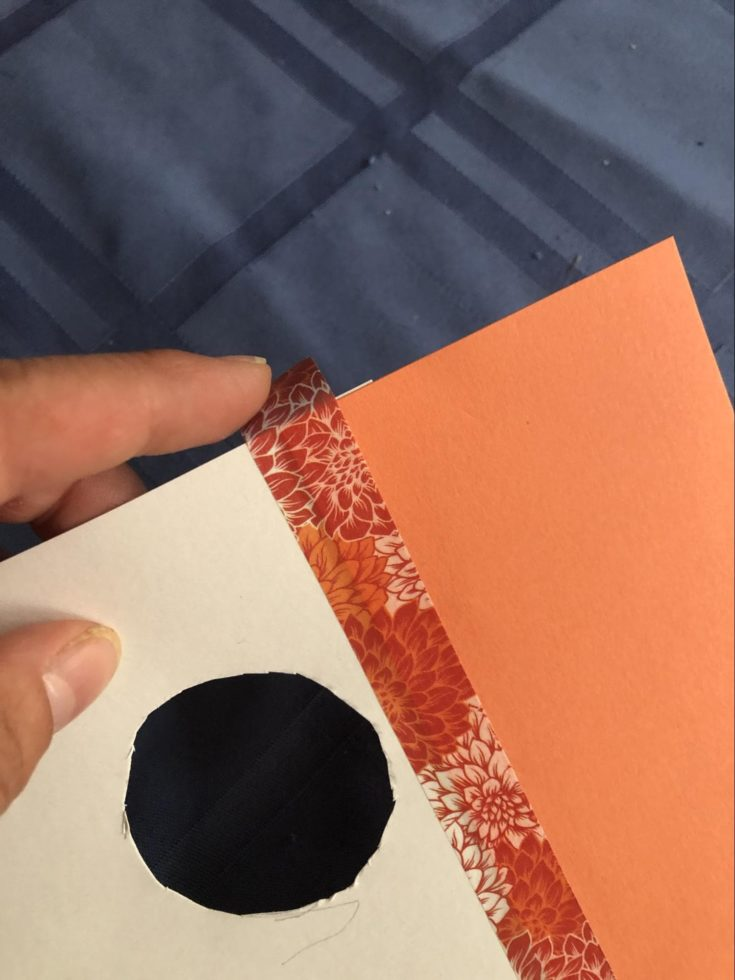 a close up shot of a hand holding a Cardboard with a hole