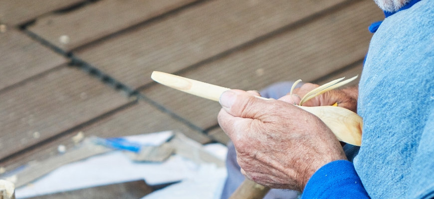 Cropped shots of old man carving a spoon.