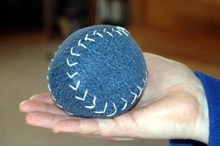 a hand holding a baseball made from a cloth