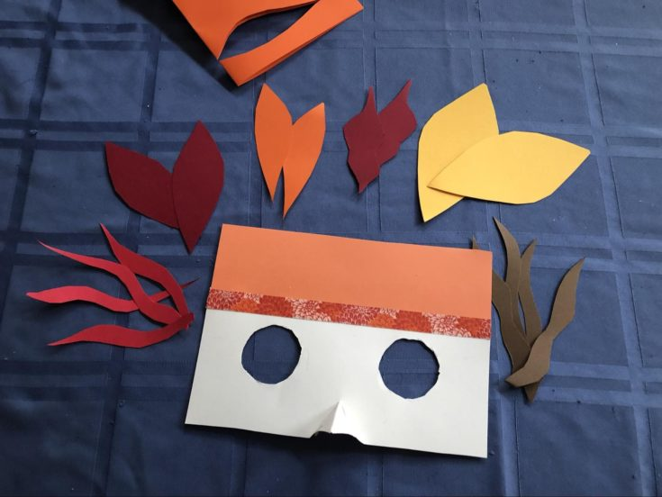 Colored paper mask and feather cutouts
