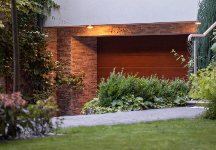 Contemporary brown closed garage door seen from the garden