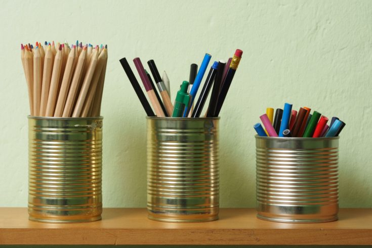 Crayons and pens in waste tin cans standing on a shelf.