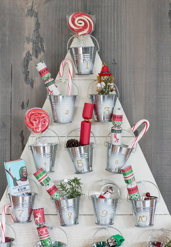 Tin Buckets hang in white board shape into a Christmas tree