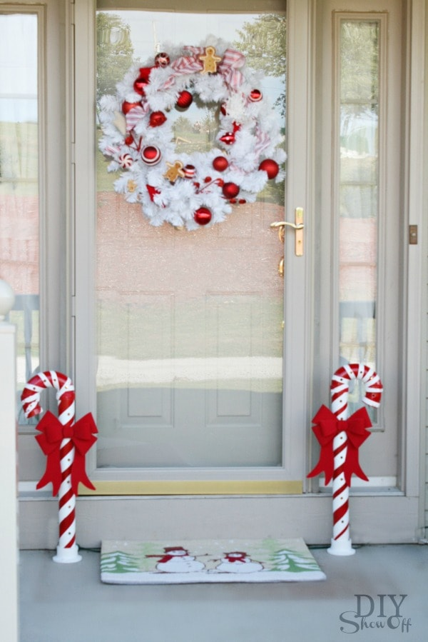 DIY Show Off PVC Candy Cane with red ribbon in front of a white door
