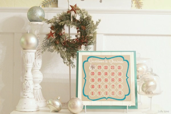 Desktop advent calendar with Christmas garland and two candle holders on top of a dresser