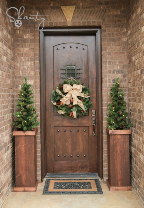 DIY Shanty 2 wooden Christmas tree stands in front of a door