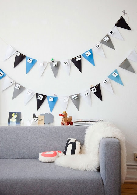 DIY colored banner on a white wall at the back of gray sofa