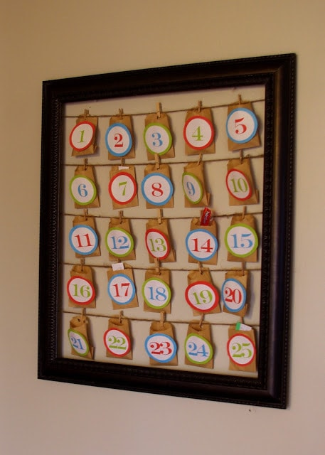 Small brown envelopes with colorful number stick on string on a black frame